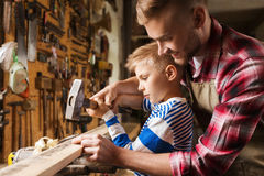 Father and son with hammer working at workshop. Happy family, carpentry, woodwork and people concept - father and little son with hammer hammering nail into wood Royalty Free Stock Photo