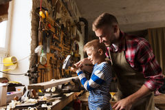 Father and son with hammer working at workshop. Happy family, carpentry, woodwork and people concept - father and little son with hammer hammering nail into wood Stock Photo
