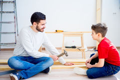 Father and son hammering nails Stock Photo