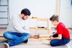 Father and son hammering nails Stock Images