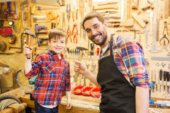 Father and son with hammers working at workshop. Family, carpentry, woodwork and people concept - father and little son with hammers at workshop Royalty Free Stock Images