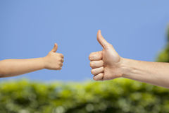 Father and son hands giving like on nature background Royalty Free Stock Photography