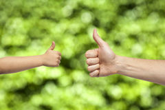 Father and son hands giving like on nature background Stock Photo