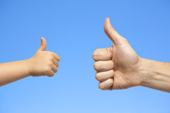 Father and son hands giving like on sky background Stock Photo