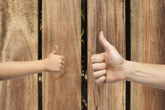 Father and son hands giving like on wooden background Royalty Free Stock Photos