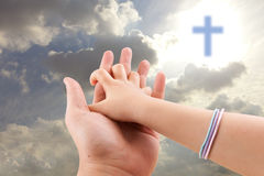 Father and son hands praying. With holy sky on holy sky with cross background stock photo