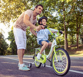 Father and son. Handsome father is teaching his cute little son riding bike in park. Both are looking forward and smiling Royalty Free Stock Photography