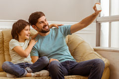 Father and son. Handsome young father in casual clothes and his cute little son making a photo using a smart phone while sitting on a sofa in the room Royalty Free Stock Photos