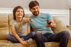 Father and son. Handsome young father in casual clothes and his cute little son watching a TV while sitting on a sofa in the room. A little boy pointing, his Royalty Free Stock Photos