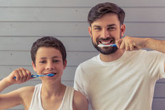 Father and son. Handsome young father and his teenage son are brushing teeth, looking at camera and smiling, against gray wall stock photos