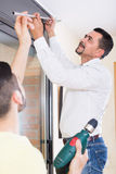 Father and son hanging curtain rod. Positive senior father and son hanging the curtain rod at home stock photo