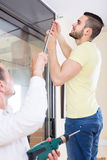 Father and son hanging curtain rod Royalty Free Stock Photo