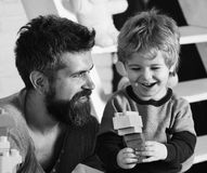 Father and son with happy faces create colorful constructions. With toy bricks. Dad and kid build out of plastic blocks. Family and childhood concept. Man and royalty free stock images