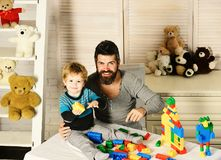 Father and son with happy faces make house with colored bricks. Family and childhood concept. Dad and kid build of. Plastic blocks. Man with beard and boy play stock photography