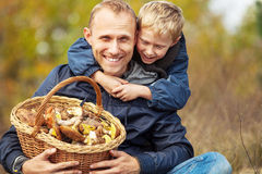 Father and son are happy that they have found a basket full of mushrooms Royalty Free Stock Image