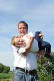 Father and son - happy together. Father holding his laughing son in arm Royalty Free Stock Photography
