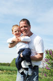 Father and son - happy together. Father holding his laughing son in arm Stock Photo