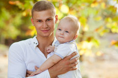 Father and son. Happy young men holding a smiling 7-9 months old baby Stock Photos