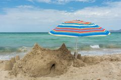 Big sandcastle and umbrella on the beach with sea in the background stock photography