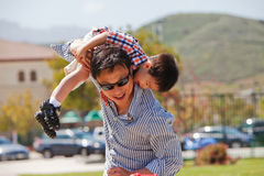 Father and son have fun. Father plays with his little son by putting him on his shoulder Stock Photos