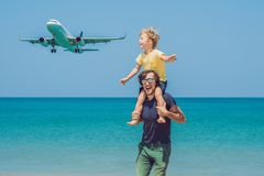 Father and son have fun on the beach watching the landing planes. Traveling on an airplane with children concept royalty free stock photos