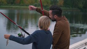 Father and son have fun on fishing stock footage