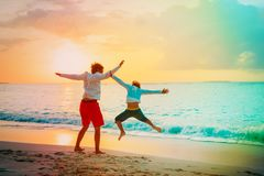 Father and son have fun jump at sunset beach. Father and son have fun jump at sunset tropical beach Stock Photos