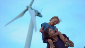 Father and son have fun standing under the wind electric generator on top of the hill by the sea. Clean energy concept. Renewable energy source stock video