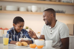 Father and son having breakfast in kitchen Royalty Free Stock Photo