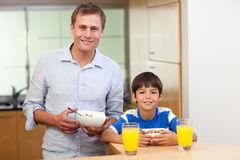 Father and son having cereals and orange juice Stock Image