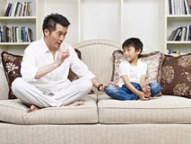 Father and son. Having a conversation on couch at home Stock Images