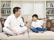 Father and son. Having a conversation on couch at home Stock Image