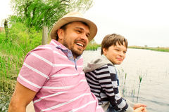 Father and son having fun. Father in the hat and a son having fun laughing on the lake royalty free stock images