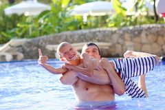 Father and son having fun in aqua park. Young family, father with child, happy teenage boy, having fun together playing in swimming pool in outdoors aquapark Royalty Free Stock Photography