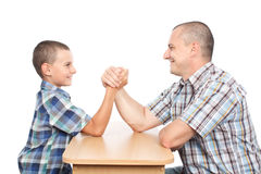 Father and son having fun with arm wrestling. Father and son arm wrestling for fun, isolated on white background Royalty Free Stock Images