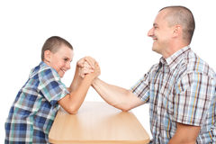Father and son having fun with arm wrestling. Father and son arm wrestling for fun, isolated on white background Stock Photo