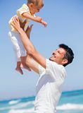 Father and son having fun on beach Stock Images