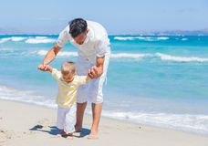 Father and son having fun on beach royalty free stock photo