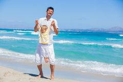 Father and son having fun on beach stock photos