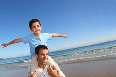Father and son having fun on the beach. Father holding son on his shoulders at the beach Stock Photography
