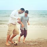 Father and son having fun on beach and playing with a ball Royalty Free Stock Images