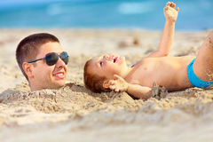 Father and son having fun on the beach Royalty Free Stock Image