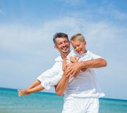 Father and son having fun on the beach Stock Images