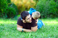 Father and son having fun on green field Royalty Free Stock Photography