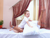 Father and son having fun at home, pillow fight Stock Photo