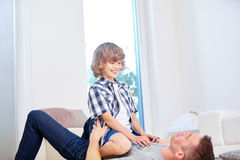 Father and son having fun at home. Father and son playing around and having fun at home in the living room Stock Images