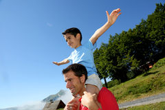 Father and son having fun in the mountains. Daddy carrying son on his shoulders Stock Photos