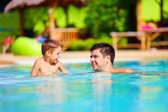 Father and son having fun in outdoor pool, summer vacation Royalty Free Stock Image