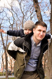 Father and son having fun outdoors on a spring sunny day. Happy smiling little boy in the arms of his dad. Concept of happy family life, love and happiness Royalty Free Stock Image