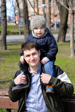 Father and son having fun outdoors on a spring sunny day. Happy smiling little boy in the arms of his dad. Concept of happy family life, love and happiness Royalty Free Stock Photo